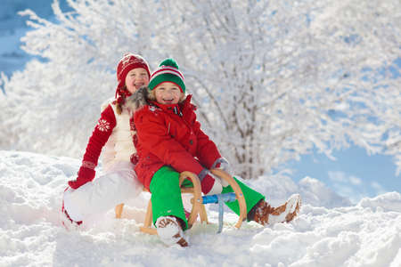 Little girl and boy enjoying sleigh ride. Child sledding. Toddler kid riding a sledge. Children play outdoors in snow. Kids sled in snowy park in winter. Outdoor fun for family Christmas vacation. 版權商用圖片 - 112620853