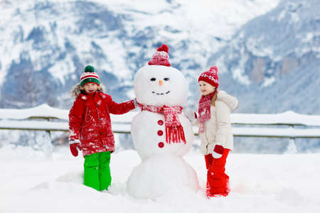 Child building snowman. Kids build snow man. Boy and girl playing outdoors on snowy winter day. Outdoor family fun on Christmas vacation in the mountains. Children play in Swiss mountain landscape. Фото со стока