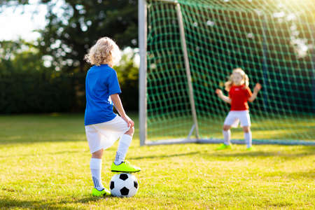 Kids play football on outdoor field. Children score a goal during soccer game. Little boy kicking ball. Running child in team jersey and cleats. School football club. Sports training for young player.