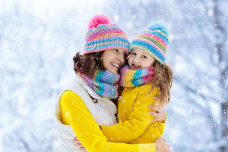 Mother and child in knitted winter hats play in snow on family Christmas vacation. Handmade wool hat and scarf for mom and kid. Knitting for kids. Knit outerwear. Woman and little girl in snowy park. 免版税图像