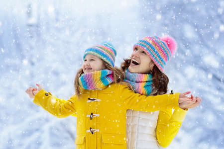 Mother and child in knitted winter hats play in snow on family Christmas vacation. Handmade wool hat and scarf for mom and kid. Knitting for kids. Knit outerwear. Woman and little girl in snowy park. Stock Photo