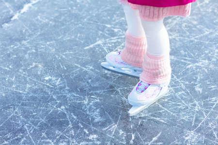 Enfant patinant sur la glace naturelle le jour d'hiver ensoleillé. Enfants avec des patins. Petite fille patinant sur un lac gelé dans un parc enneigé. Plaisirs de la neige et de l'hiver. Activité de plein air saine pour les enfants. Enfant sur la patinoire.