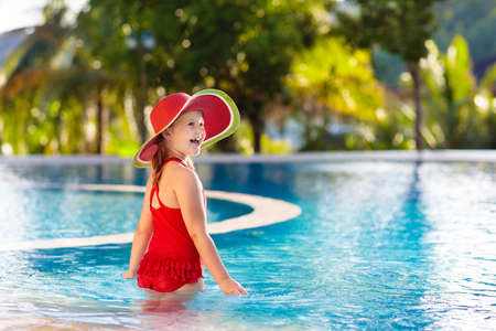 Child in swimming pool. Tropical vacation for family with kids. Little girl wearing red swimsuit and watermelon sun hat playing in outdoor pool of exotic island resort. Water and swim fun for children