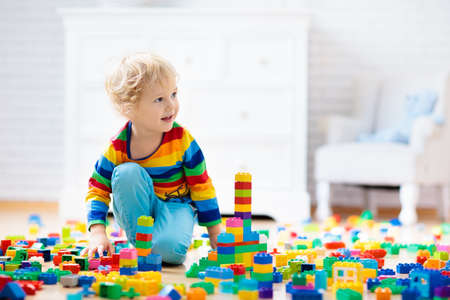 Child playing with colorful toy blocks. Little boy building tower at home or day care. Educational toys for young children. Construction block for baby or toddler kid. Mess in kindergarten play room.