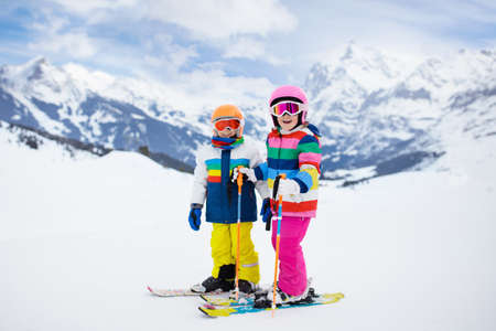 Child skiing in the mountains. Kid in ski school. Winter sport for kids. Family Christmas vacation in the Alps. Children learn downhill skiing. Alpine ski lesson for boy and girl. Outdoor snow fun. Reklamní fotografie