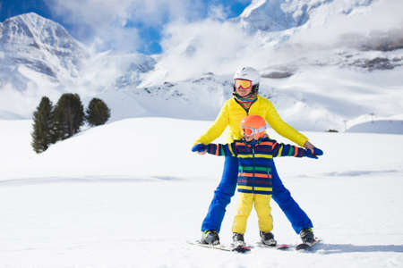 Family skiing in mountains. Mother and kids ski in Swiss Alps during winter Christmas vacation. Active outdoor sport for parents and children. Snow fun for boy and girl. Mom teaching kids to ski.