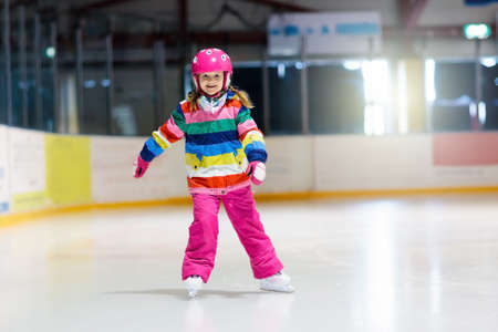 Child skating on indoor ice rink. Kids skate. Active family sport during winter vacation and cold season. Little girl in colorful wear training or learning ice skating. School sport activity and clubs