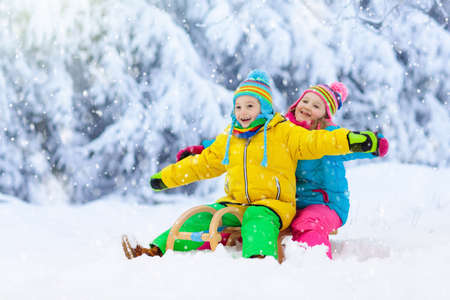 Little girl and boy enjoying sleigh ride. Child sledding. Toddler kid riding a sledge. Children play outdoors in snow. Kids sled in snowy park in winter. Outdoor fun for family vacation.