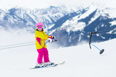 Child on a button ski lift going uphill in the mountains on a sunny snowy day. Kids in winter sport school in alpine resort. Family fun in the snow. Little skier learning and exercising on a slope. Stock Photo