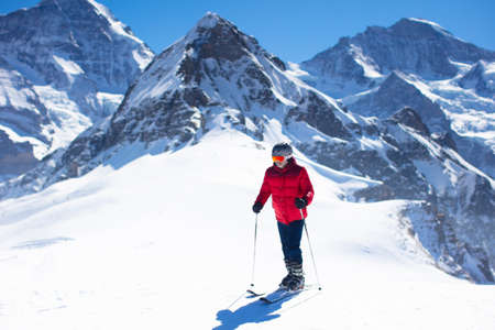 Man skiing in Alps mountains. Ski and snow fun on winter vacation. Backcountry skiing. Snow peaks and mountain landscape. Extreme outdoor sports. Hiking in winter. Alpine skiing holiday.