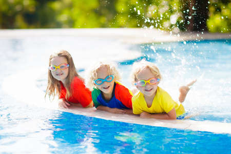 Kids play in swimming pool. Children learn to swim in outdoor pool of tropical resort during family summer vacation. Water and splash fun for young kid on holiday. Sun protection for child and baby. Foto de archivo - 116565164