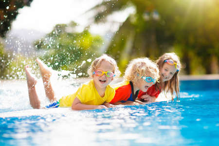 Kids play in swimming pool. Children learn to swim in outdoor pool of tropical resort during family summer vacation. Water and splash fun for young kid on holiday. Sun protection for child and baby. Banque d'images - 116565170