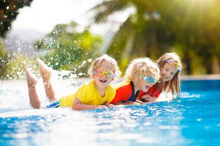 Kinder spielen im Schwimmbad. Kinder lernen im Sommerurlaub mit der Familie im Außenpool des tropischen Resorts zu schwimmen. Wasser- und Spritzspaß für kleine Kinder im Urlaub. Sonnenschutz für Kind und Baby.
