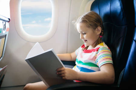 Child in airplane. Kid with book in air plane sitting in window seat. Flight entertainment for kids. Traveling with young children. Kids fly and travel. Family vacation. Girl reading book in airplane. Stockfoto