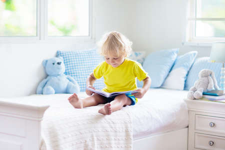 Child playing in bed in white sunny bedroom with window. Kids room and interior design. Baby boy at home. Bedding and textile for children nursery. Kid with toy and book. Nap and sleep time. Stock Photo