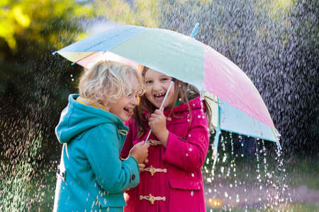 Kids with colorful umbrella playing in autumn shower rain. Coat in rainy weather. Fall outdoor fun for children. Kid catching rain drops. Foto de archivo - 116565247