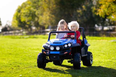 Bambini che guidano una macchinina elettrica nel parco estivo. Giocattoli all'aperto. Bambini in un veicolo a batteria. Ragazzino e ragazza in sella a un camion giocattolo in giardino. Famiglia che gioca nel cortile di casa.