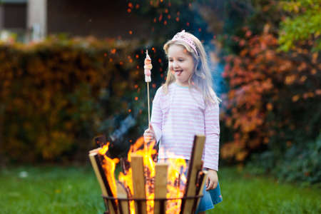 Child with smores at camp fire. Kids roast marshmallow on stick at bonfire. Autumn family outdoor fun. Camping with children in fall forest. Little girl roasting marshmallows. Stock Photo