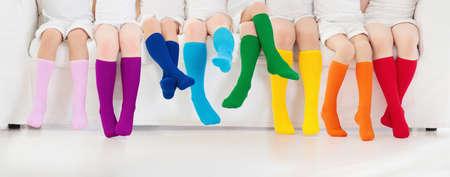 Dzieci noszą kolorowe tęczowe skarpetki. Kolekcja obuwia dziecięcego. Różnorodne podkolanówki i rajstopy z dzianiny. Odzież i odzież dziecięca. Moda dziecięca. Nogi i stopy grupy małego chłopca i dziewczynki.