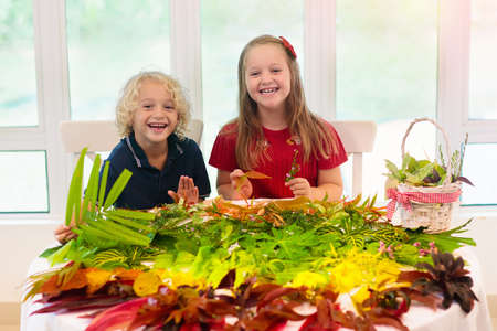 Kids pick colorful autumn leaves for school art project. Boy and girl making picture gluing fall leaf in rainbow color. Crafts for young children. Preschool and kindergarten arts homework. Reklamní fotografie - 116565431