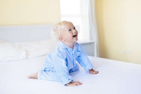 Kids playing in parents bed. Children wake up in sunny white bedroom. Little boy in blue pajamas. Sleepwear and bedding for child and baby. Nursery interior for toddler kid. Family morning. Foto de archivo