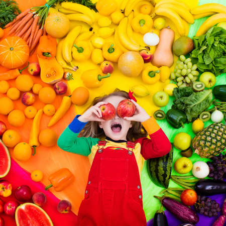 Little girl with variety of fruit and vegetable. Colorful rainbow of raw fresh fruits and vegetables. Child eating healthy snack. Vegetarian nutrition for kids. Vitamins for children. View from above. Archivio Fotografico - 116565626
