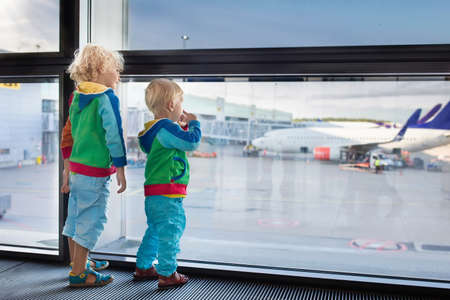 Kids at airport. Children look at airplane. Traveling and flying with child. Family at departure gate. Vacation and travel with young kid. Boy and baby before flight in terminal. Kids fly a plane.