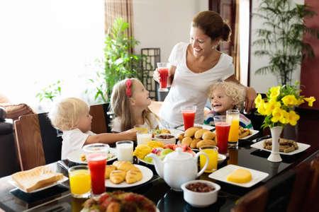Zdrowe rodzinne śniadanie w domu. Matka i dzieci jedzą owoce tropikalne, chleb tostowy, ser i kiełbasę. Dzieci piją świeżo wyciśnięty sok w słoneczny poranek. Mama, chłopiec, dziewczynka i dziecko jedzą śniadanie.