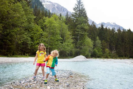 Children hiking in Alps mountains crossing river. Kids play in water at mountain in Austria. Spring family vacation. Little boy and girl on hike trail. Outdoor fun. Active recreation with children.