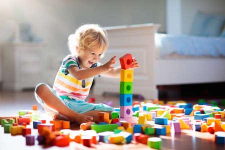 Kind, das mit bunten Spielzeugklötzen spielt. Kinderspiel. Kleiner Junge, der Turm aus Blockspielzeug auf dunklem Boden im sonnigen weißen Schlafzimmer baut. Lernspiel für Baby und Kleinkind. Kinder bauen Spielzeughaus