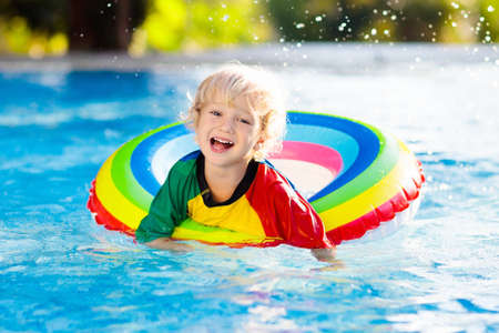 Child in swimming pool floating on toy ring. Kids swim. Colorful rainbow float for young kids. Little boy having fun on family summer vacation in tropical resort. Beach and water toys. Sun protection. Foto de archivo - 116566095