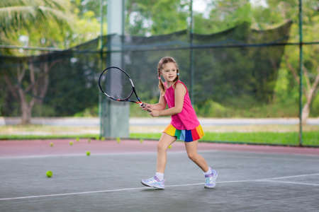 Bambino che gioca a tennis sulla corte interna. Bambina con racchetta da tennis e palla nel club sportivo. Esercizio attivo per i bambini. Attività estive per bambini. Formazione per ragazzino. Bambino che impara a giocare. Archivio Fotografico