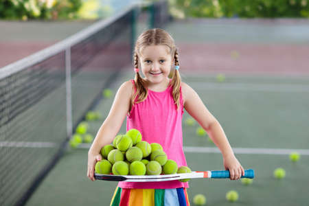 Child picking up balls after tennis match at outdoor court. Little girl gathering ball on racket after training in sports club. Healthy sport activity for kids. Children tidy up after game. Banque d'images - 116566139