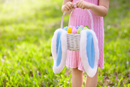 Kids with eggs basket and bunny ears on Easter egg hunt in sunny spring garden. Little girl searching for colorful candy and chocolate eggs with rabbit basket. Children celebrating Easter.