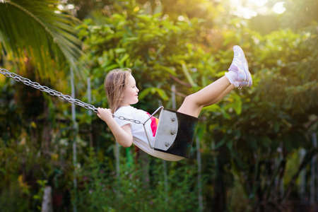 Child swinging on playground on sunny summer day in a park. Kids swing. School or kindergarten yard and play ground. Little girl flying high in the air on swing. Summer outdoor activity. Kid playing.