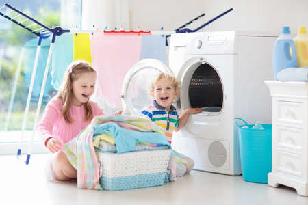 Children in the laundry room with washing machine or tumble dryer. Kids help with family chores. Modern household devices and washing detergent in white sunny home. Clean washed clothes on drying rack.