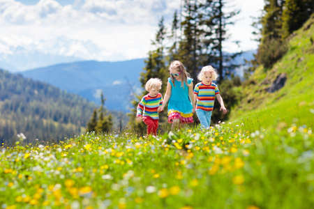 Children hiking in Alps mountains. Kids run at snow covered mountain in Austria. Spring family vacation. Little boy and girl on hike trail in blooming alpine meadow. Outdoor fun and healthy activity. Standard-Bild - 116566213