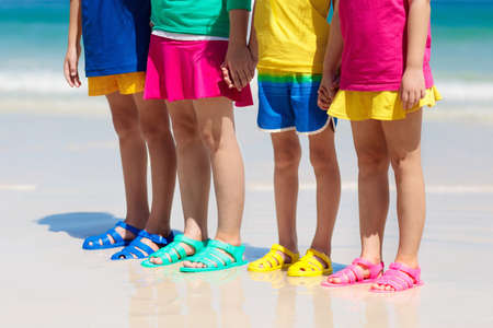 Kids beach shoes. Colorful footwear for boy or girl. Group of children wearing aqua shoe playing on tropical beach on summer vacation. Water and sand fun. Feet and legs of boys, girls. Sun protection.
