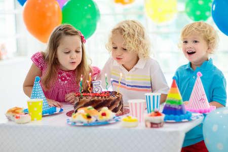 Fête d'anniversaire pour enfants. Enfant soufflant des bougies sur un gâteau coloré. Maison décorée avec des bannières de drapeau arc-en-ciel, des ballons. Célébration du thème des animaux de la ferme. Petit garçon célébrant son anniversaire. Nourriture de fête.