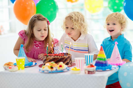 Kids birthday party. Child blowing out candles on colorful cake. Decorated home with rainbow flag banners, balloons. Farm animals theme celebration. Little boy celebrating birthday. Party food. Stock Photo
