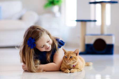 Niño jugando con gato en casa. Niños y mascotas. Niña alimentando y acariciando lindo gato color jengibre. Árbol de gatos y rascador en el interior de la sala de estar. Los niños juegan y alimentan al gatito. Animales domésticos.