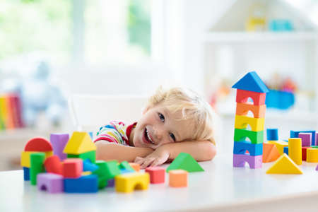 Kid playing with colorful toy blocks. Little boy building tower of block toys. Educational and creative toys and games for young children. Baby in white bedroom with rainbow bricks. Child at home. Stockfoto