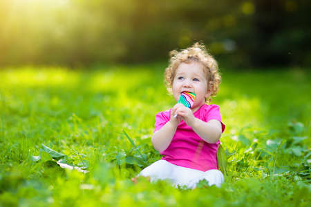 Baby girl eating ice cream candy in sunny park. Child with lollipop. Kids play outdoors in summer. Toddler with sweet snack. Children eat sweets. Kid  with unhealthy sugar treat.