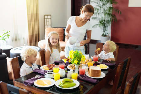 Healthy family breakfast at home. Mother and kids eating tropical fruit, toast bread, cheese and sausage. Children drink fresh pressed juice on sunny morning. Mom, boy, girl and baby eat breakfast. Banco de Imagens