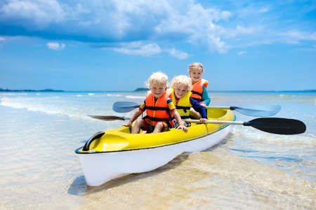 Kids kayaking in ocean. Children in kayak in tropical sea. Active vacation with young kid. Boy and girl in canoe on beautiful beach. Holiday activity with preschool child. Family water fun. Stockfoto
