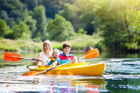 Child with paddle on kayak. Summer camp for kids. Kayaking and canoeing with family. Children on canoe. Family on kayak ride. Wild nature and water fun on summer vacation. Camping and fishing.
