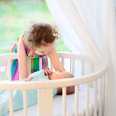 Sister and baby brother. Little girl meeting newborn sibling. Kids in bed. Two children playing together in a white sunny bedroom. Siblings play indoors. Infant boy in a white bassinet. Kid in a crib. Stock Photo