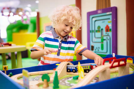Kids play toy railroad. Little blond curly boy with wooden trains in indoor playground or amusement center. Child with car and train toys at home or daycare. Kindergarten or preschool play room. Banco de Imagens