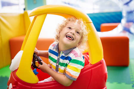 Child riding toy car. Little boy playing with big bus. Kid driving plastic truck in indoor playground or kindergarten. Toddler at day care play room. Toys for little boys. Daycare amusement center.