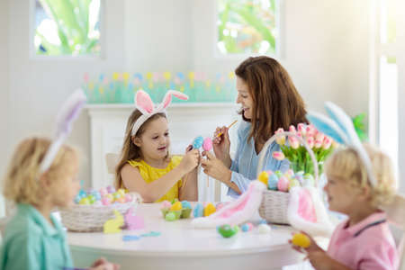 Mother and kids color Easter eggs. Mom, little girl and boy with bunny ears dying and painting for Easter egg hunt in white sunny room. Family celebration and home decoration for spring holiday. Stock Photo